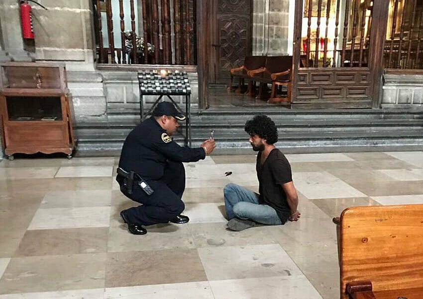 Police officer takes a photo of priest's alleged attacker.