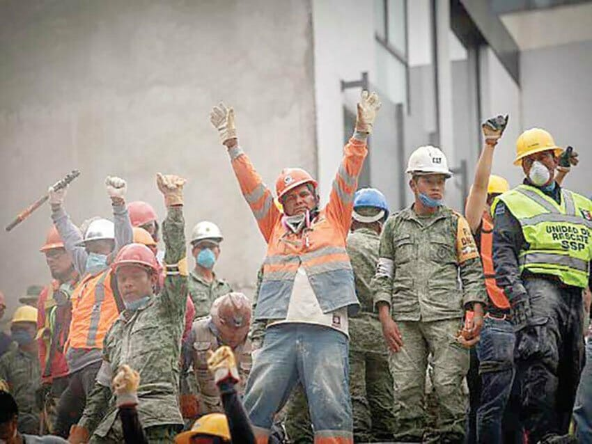 Rescue workers call for quiet as they listen for voices in the rubble.
