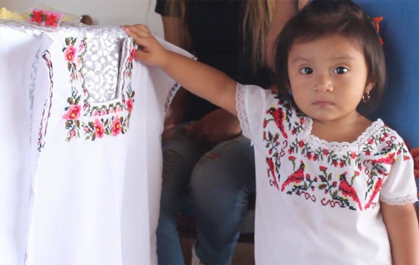 A young model exhibits embroidery from Tekax.