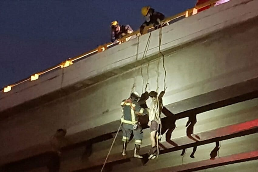 Emergency personnel retrieve a body hanging from a bridge this morning.
