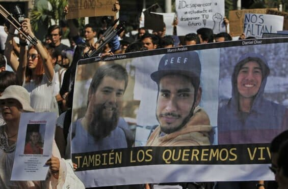 A poster of the three victims is displayed during a protest in Jalisco.