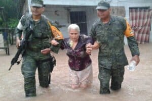 Military personnel help a woman from her flooded home.