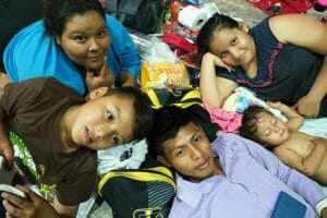 A family poses in their makeshift beds for the night in Arriaga.