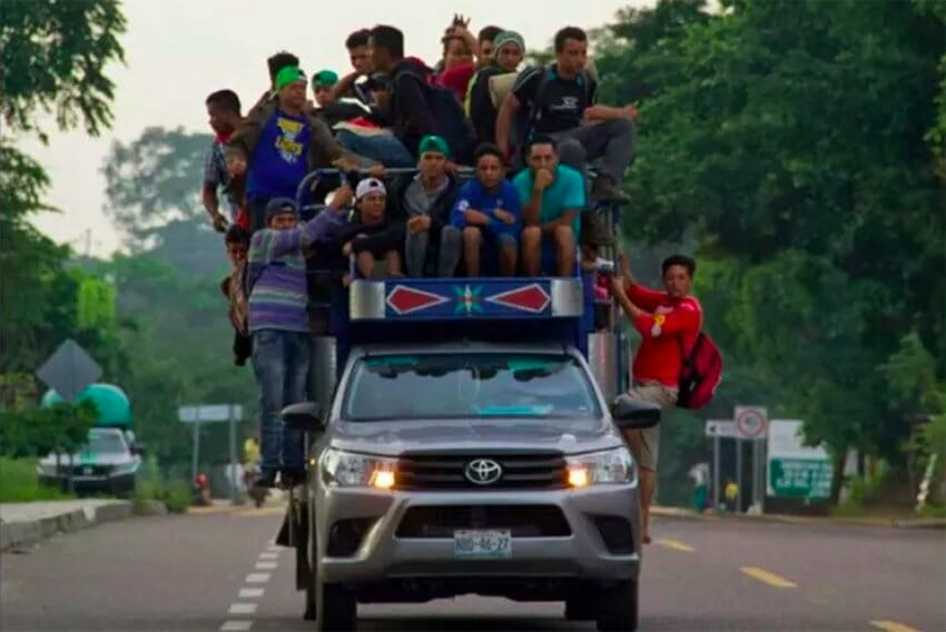Migrants hang off a truck en route to Mexico City.