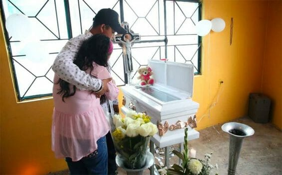 Parents grieve at the coffin of one of the victims of a bacterial infection.