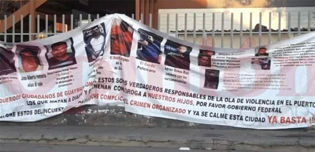 The banner identifying alleged criminals was hung this morning outside a school.