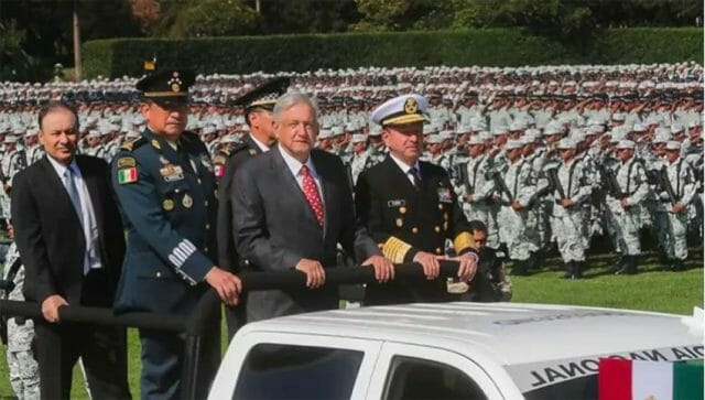 Flanked by the heads of the army and navy, the president inspects the National Guard on Monday.