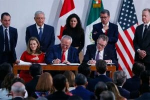López Obrador and other officials witness the signing of the accord.