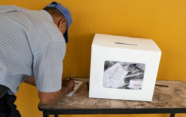 A man casts his ballot in the Maya Train vote in December.