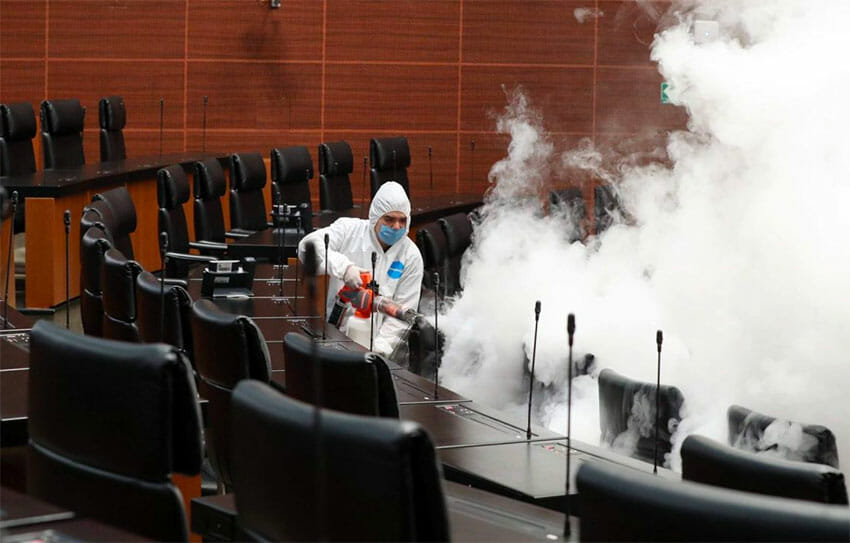 A worker sprays disinfectant in the Senate.