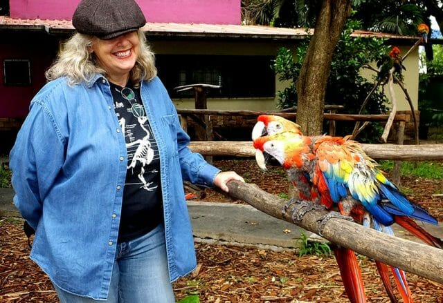 Parque Urbano manager Karina Aguilar with two rescued macaws.