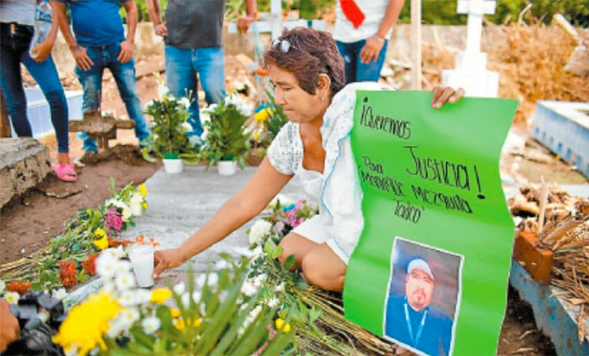 A woman places flowers at the grave of lynching victim Manrique Mezquita.