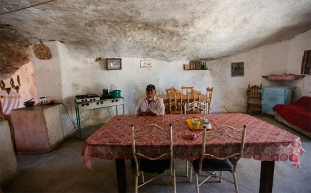 Hernández inside a room that serves as living room, kitchen and dining room.