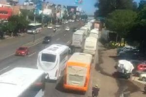 A convoy of buses carries students to a protest.