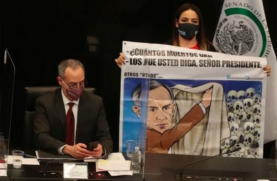 A senator holds a cartoon of López-Gatell, left, during his appearance in the Senate.