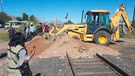 A backhoe clears one of eight blockades in Chihuahua on Sunday.