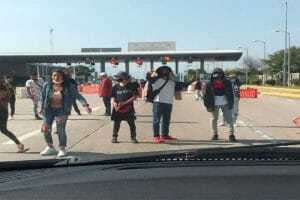 A motorist approaches toll plaza extortionists in Morelos.