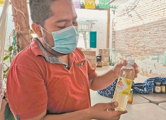 Joel Luis and a bottle of sauce made by El Típico in Ixtepec.