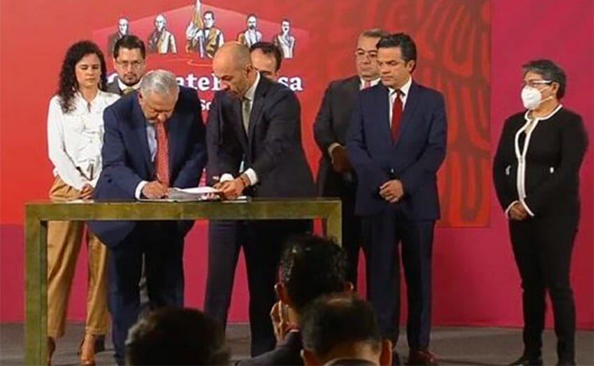 The president signs the proposal Thursday at the morning press conference.