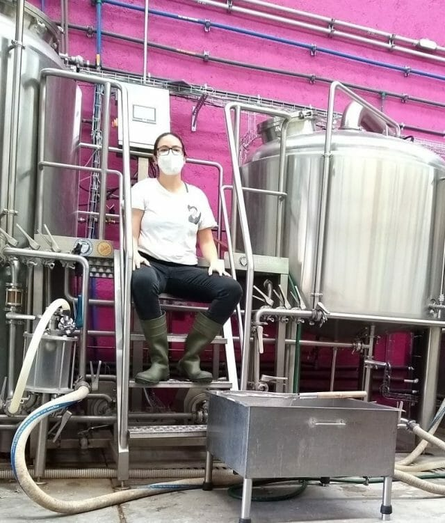Domínguez surrounded by her brewing equipment.