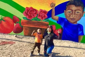 Artist Julia Celeste with budding painter Edgar in front of a mural in the Las Misiones neighborhood of San Quintín, depicting principal crops of the Valley.