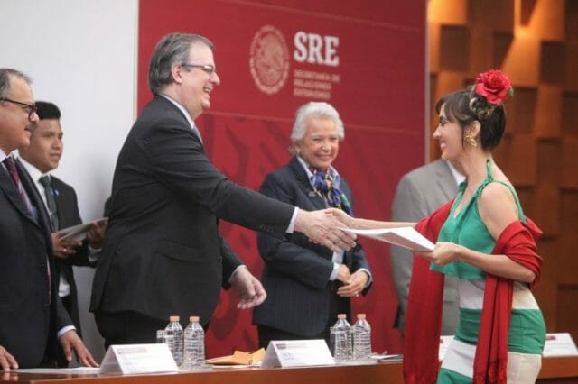 A woman receives her Mexican citizenship papers from Foreign Secretary Marcelo Ebrard and Interior Minister Olga Sánchez Cordero in 2019.