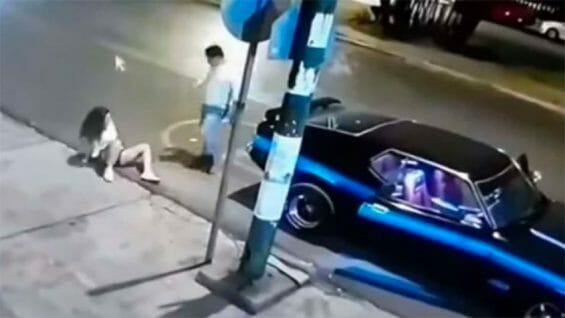 The woman sits on the road after being pushed out of the car.
