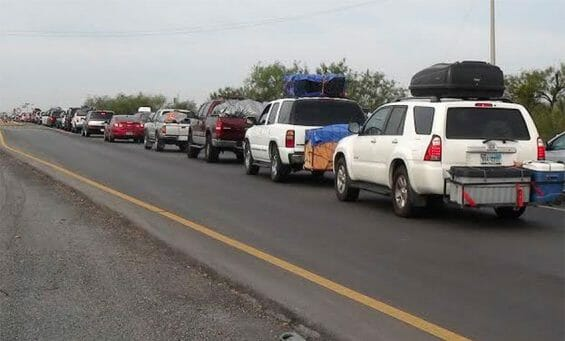 A convoy of vehicles is escorted by police to provide security.