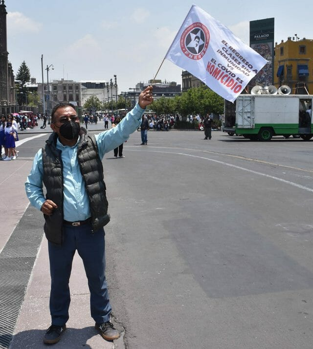 """""""A return to classes without Covid immunity is murder,"""" a Mexico City protester's flag says."""