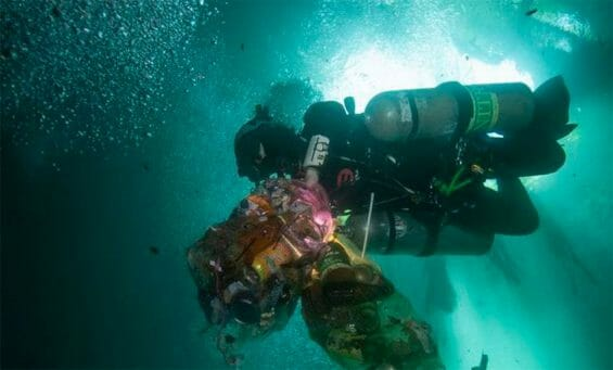 A diver with bags of waste recovered from a cenote.