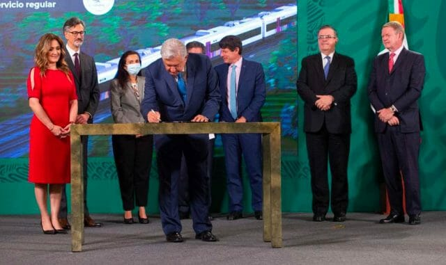 Foreign dignitaries, contractors and officials watch as the president signs a contract for the Maya Train.