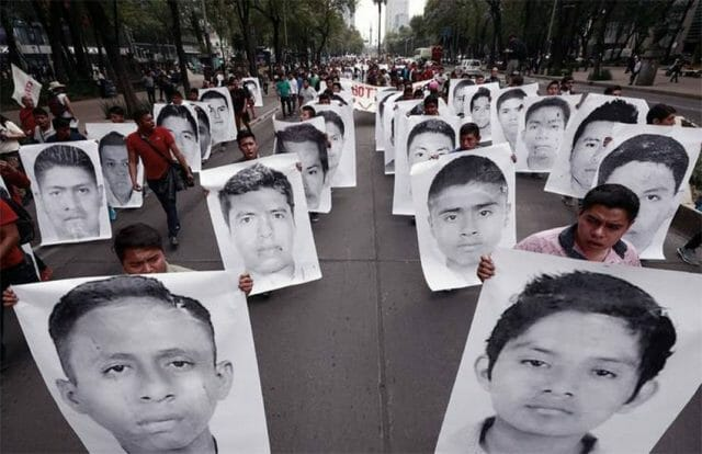 Protesters carry signs showing the faces of the disappeared Ayotzinapa students