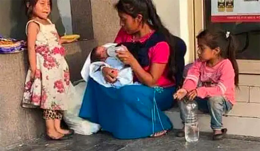 The young mother feeds the baby that was left in her care in downtown Monterrery.