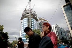 People walk by a building under construction in Mexico City