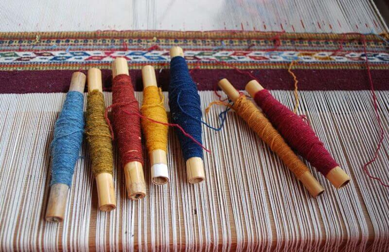 Skeins of yarn colored traditionally with natural dyes ready for weaving