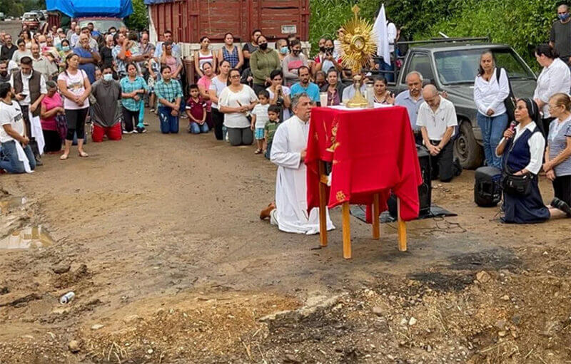 Rev. José Luis Martínez Chávez leads mass next to the place where an armed group destroyed the road, blocking access into town.