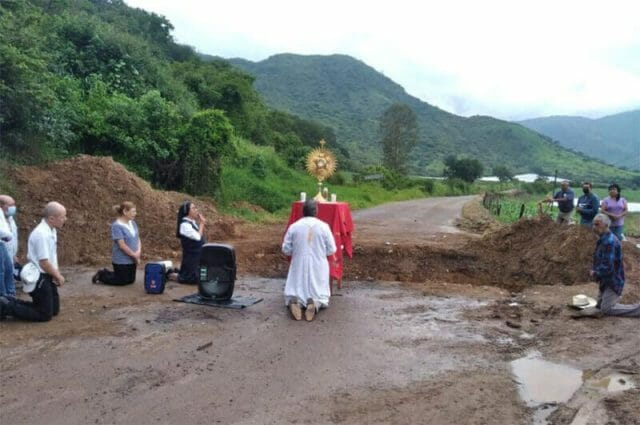 The priest prays in front of one of the ditches dug by armed groups to block access to Coalcomán.