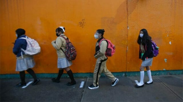 Face masks in place, students make their way to school Monday morning.