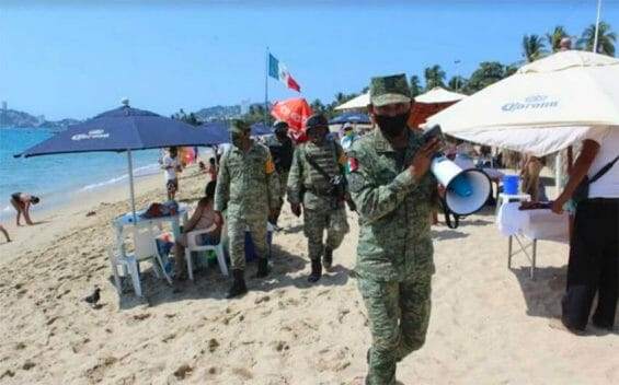 Soldiers patrol an Acapulco beach earlier this year to remind visitors to follow coronavirus precautions.