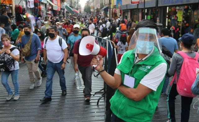 Crowds of masked pedestrians in the streets of Mexico City.
