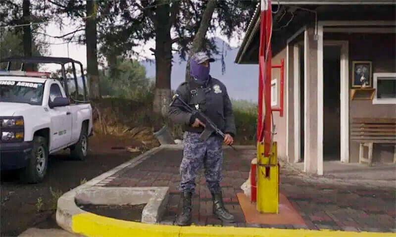 In a still from the documentary, a member of the community's voluntary security force stands guard.