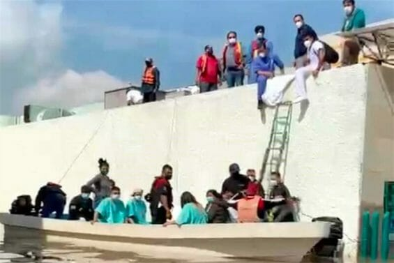 People are evacuated by boat Tuesday from the Tula General Hospital.