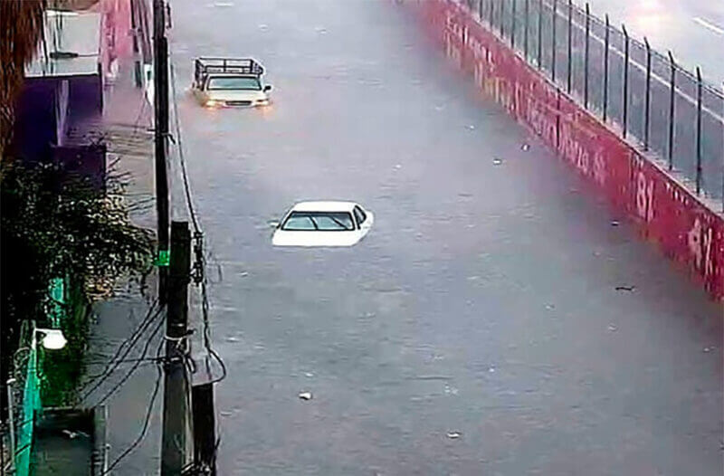 Nearly submerged vehicles on a road in Ecatepec.