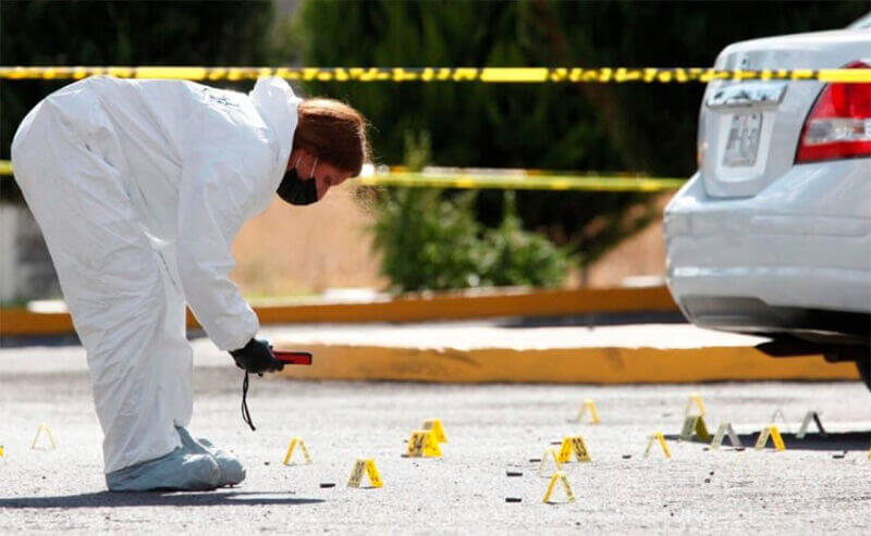 A forensic expert studies bullet casings at a Jalisco crime scene in 2020.