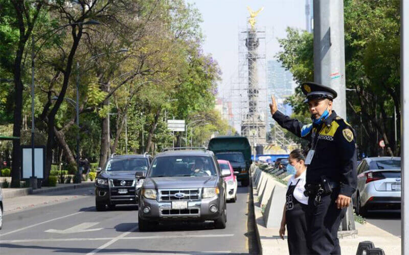 A transit police officer directs traffic at a Mexico City crosswalk.