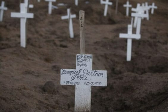 A man's name written in marker on the white cross that adorns a mass grave