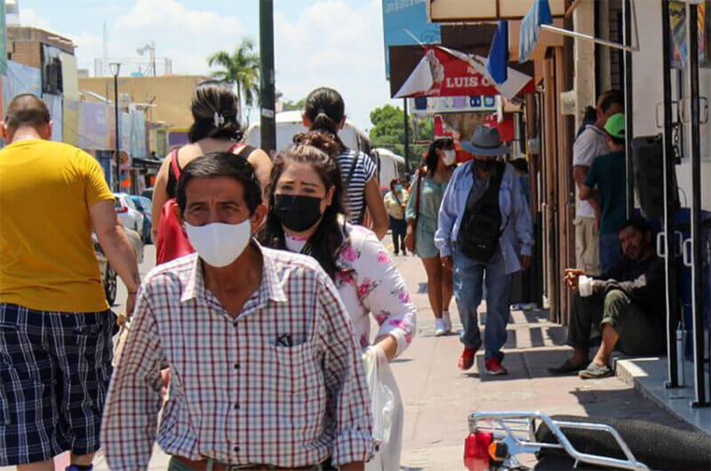Residents with face masks make their way through downtown Hermosillo, Sonora.